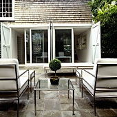 Metal terrace furniture with white cushions facing a bank of windows with open shutters
