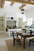 A dining table and a kitchen table in a rustic kitchen in a country house with a wood beam ceiling