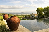 Amphorae by a pool with a view of a country house in the Mediterranean landscape