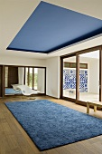 A minimalistic room - a blue rug on the floor boards and a blue-painted ceiling area