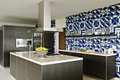 A designer kitchen - a marble work surface on a grey kitchen counter with an extractor fan and a blue and white-tiled wall
