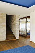 An anteroom with walnut floor boards and a wooden staircase built into a natural stone wall and a view of a window