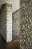 A natural stone wall with a floor-to-ceiling access gap giving a view of the stairwell