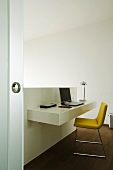 A minimalistic home office - a low partition wall with a shelf and an upholstered chair