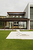 Loungers on a white stone patio in a garden of a house with lots of windows and a wooden porch