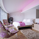 A floral patterned armchair and a television in front of a bed and indirect coloured lighting