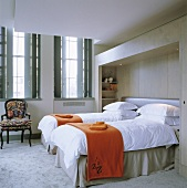 Orange throws on two single beds in a room with windows with shutters on the inside