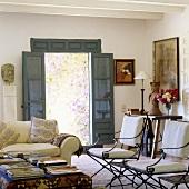 Padded metal chairs in the living room of a country house with an open garden door