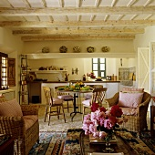 A living room-cum-kitchen with wicker chairs in a simple Mediterranean country house