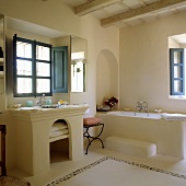 A stone, Spanish-style bathroom with blue window and inside shutters