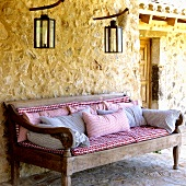 A Mediterranean country house - a rustic bench with checked upholstery and lanterns hanging on the exterior, natural stone walls