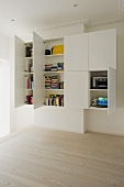 White, tailor-made cupboard with open doors in a period building