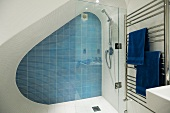 A designer shower cubicle in an attic with blue wall tiles and a stainless steel towel rack
