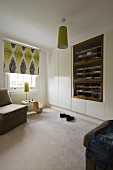 A bedroom with a built-in wardrobe, an open shelf and a ceiling lamp with a green shade