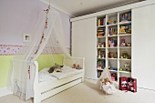 A child's bedroom - a child's bed with a canopy and a built-in shelf with sliding doors