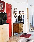 A hallway in an apartment with a red door and a wooden chest of drawers