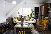 Maisonette apartment living - a coffee table and a wicker chair with a flight of stairs in the background