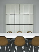 A conference table with brown bucket chairs and a tailor-made wall cupboard with open doors