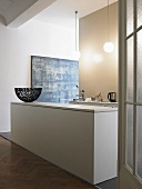 An open-plan kitchen in a minimalistic anteroom - a basket on a white monolithic kitchen counter