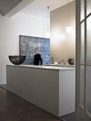 An open-plan kitchen in a minimalistic anteroom - a white monolithic kitchen counter and a man in the hallway