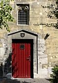 A red door in a stone facade of a church