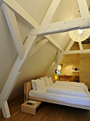 A designer wooden bed in an attic room with wooden beams