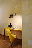 A minimalistic study corner under a slopping roof - a classical yellow chair in front of the desk and a natural stone wall