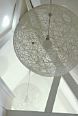 A view of a round designer ceiling lamp made of meshwork