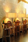 Illuminated bar tables - designer bar tables with stools and floor lamps in front of a natural stone wall