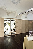 A designer restaurant with a vaulted ceiling - a modern built-in cupboard with a wine rack and a dark wooden floor