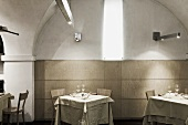 Restaurant tables in an arched niche with decorative lighting