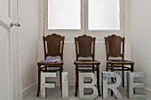 An artistic room installation - metal letters in front of antique chairs