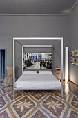 A designer four poster bed against a grey wall on a patterned terrazzo floor