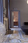 An art nouveau fireplace room with a patterned terrazzo floor and a view through a door onto a chest of drawers