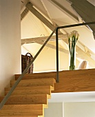 A flight of wooden stairs with a minimalistic banister and a gallery into an open attic room