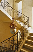 An elegant stairway - stairs with a wrought iron banister and an antique pendent lamp