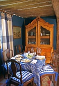 A meal in a country house - an antique cabinet against a blue wall in a room with a wood beam ceiling