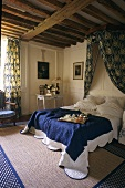 Breakfast in bed - a darkened bedroom with a canopy and a rustic wooden beam ceiling
