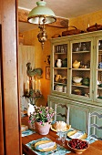 A table laid for a meal in a country house with a kitchen dresser with crockery and an antique ceiling lamp