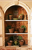 Crockery in an arched corner cupboard with its door open