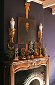 A carved wooden mantelpiece with candle holders and golden brackets on a purple wall