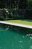 Shades of green - the reflection of water in a pool contrasting with the green on the lawn