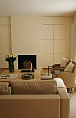 A living room with a brown sofa in front of a fireplace and a simple, built-in cupboard