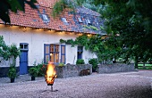 A flaming incinerator in the yard of a Flemish farm house