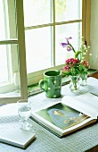A mug and an open book on the window sill of a transom window