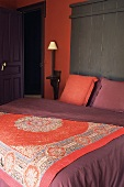 A bed with an oriental throw and a brick red wall