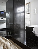 A designer bathroom - a pillar with a shower head and taps and a bathtub with grey stone tiles