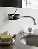 A designer wall tap over a wash basin and pieces of soap in a silver dish