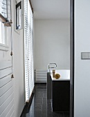 A view into a designer bathroom with a free-standing tap, a bathtub and grey floor tiles