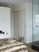 A bedroom - a fur cover on the bed and a built in cupboard with sliding doors